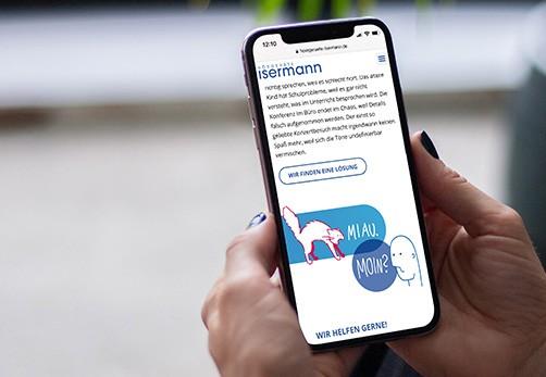 In diesem Bild sieht man ein Smartphone aus dessen Display man die Webseite der Firma Isermann Hörgeräte abgebildet ist.