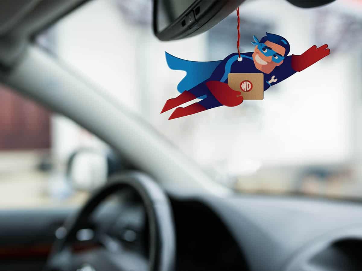 """In diesem Bild sieht man wie der """"Duft-Hero"""" von Happy Cars an einem Rückspiegel vom Auto hängt."""