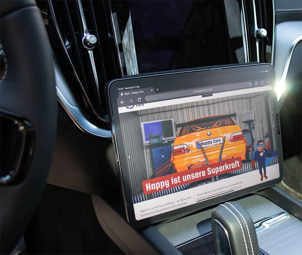 Man sieht ein Tablet in einem Auto, auf dessen Bildschirm die Webseite der Firma Happy Cars abgebildet ist.