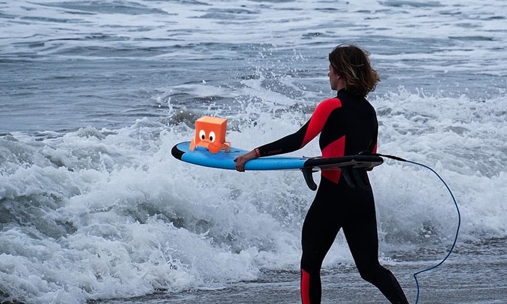 In diesem Bild sieht man eine Surferin mit ihrem Surfbrett unter dem Arm. Auf dem Surfbrett ist eine kleine Pappkrabbe.