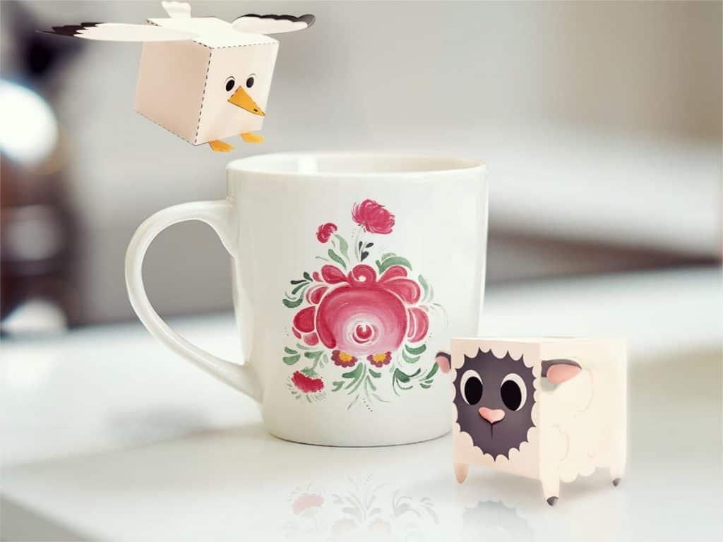 Pappfiguren eines Schaafs und einer Möwe, die an einem ostfriesischen Becher stehen.