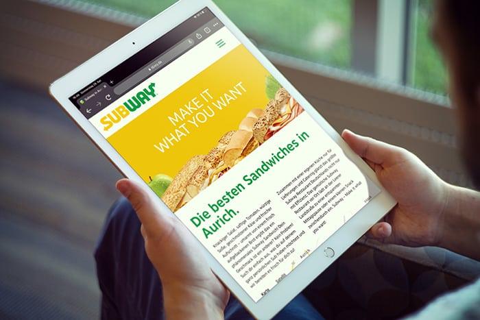 Man sieht ein Tablet auf dessen Bildschirm die Webseite von Subway abgebildet ist