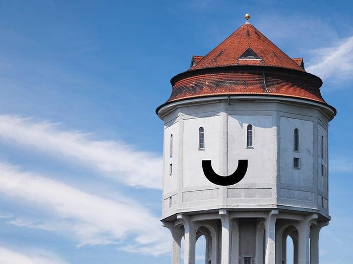 Man sieht den Emder Wasserturm mit einem Smiley Lächeln
