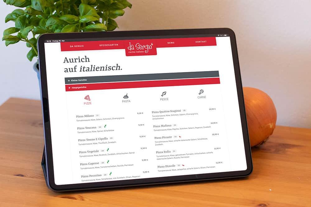 Man sieht ein Tablet auf dessen Bildschirm die Webseite von daSergio abgebildet ist.