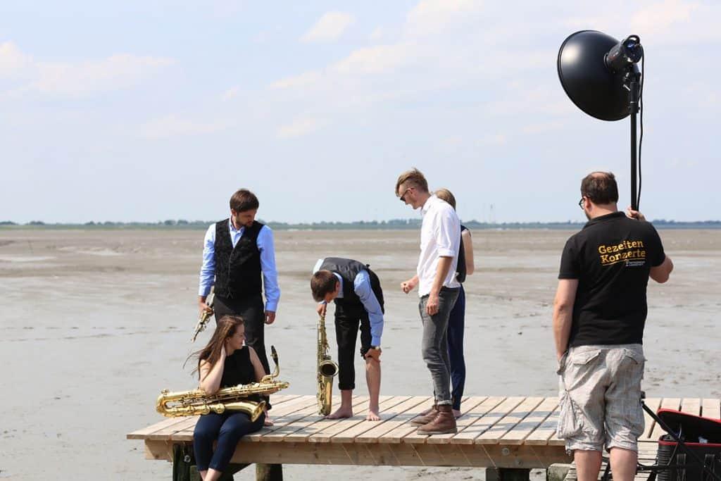 In diesem Bild sieht man 6 Personen die sich für ein Shooting vorbereiten. Im Vordergrund steht eine Person mit einem Fotolicht in der Hand. Die restlichen Personen stehen auf einem Steg in der Mitte des Bildes. Drei von diesen Personen haben Instrumente in der Hand